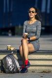 Retrato da mulher nova e atrativa que senta-se no banco e que bebe um café da manhã fotos de stock