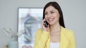 Retrato da mulher nova feliz que fala no telefone vídeos de arquivo