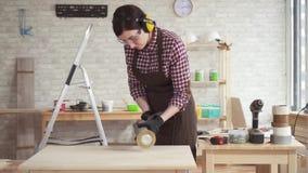 Retrato da mulher nova profissional do carpinteiro que trabalha com madeira, mo lento filme