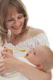 Retrato da mulher nova que alimenta seu bebê Fotos de Stock Royalty Free