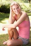 Retrato da mulher nova que relaxa no parque Fotografia de Stock Royalty Free