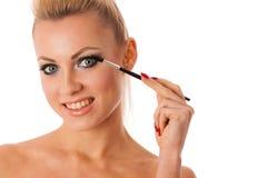 Retrato da mulher que guarda acessórios da beleza, rímel, Br do pauder Imagem de Stock