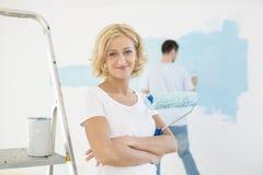 Retrato da mulher que guarda o rolo de pintura com a parede da pintura do homem no fundo Imagens de Stock