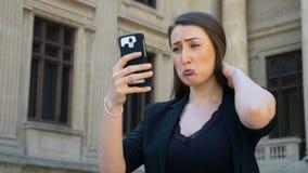 Retrato da mulher que guarda um smartphone e que toma os vídeos dos selfies que fazem a cara triste video estoque