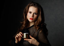 Retrato da mulher que mantém a xícara de café contra o fundo escuro Fotos de Stock Royalty Free