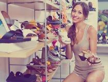 Retrato da mulher que olha confundido com os dois pares de sapatas Imagem de Stock