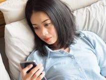 Retrato da mulher que usa o smartphone ao encontrar-se na cama fotografia de stock