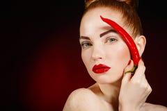 Retrato da mulher ruivo bonita com pimenta de pimentão picante encarnado de pimenta de Caiena Imagens de Stock Royalty Free
