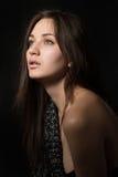Retrato da mulher só nova na sala escura Fotografia de Stock Royalty Free