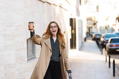 Retrato da mulher satisfeito que bebe o café afastado ao andar através da rua da cidade fotografia de stock