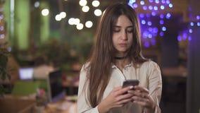 Retrato da mulher segura na mensagem texting do vestuário formal branco da blusa no telefone celular da pilha no escritório ou no video estoque
