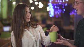 Retrato da mulher segura no vestuário formal branco da blusa com telefone celular da pilha nas mãos no escritório Homem de sorris filme