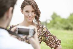 Retrato da mulher segura que está sendo fotografada pelo homem no parque imagens de stock
