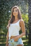 Retrato da mulher 'sexy' no pulverizador da água com a camisa branca de T Tem uma boa pele delicada, postura sensual, e sorri Fotos de Stock