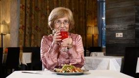 Retrato da mulher superior atrativa no suco de fruta fresco do gosto do restaurante Conceito feliz da senilidade Sorriso e lughin filme