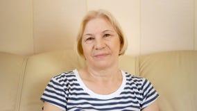 Retrato da mulher superior bonita alegre que senta-se no sofá em casa Tendo o bom tempo que relaxa vídeos de arquivo