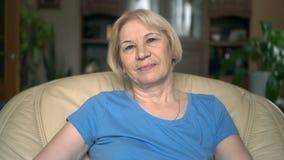 Retrato da mulher superior bonita de sorriso que senta-se na cadeira em casa Tendo o bom tempo que relaxa vídeos de arquivo