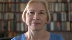 Retrato da mulher superior de sorriso feliz bonita em casa Estantes da biblioteca no fundo vídeos de arquivo
