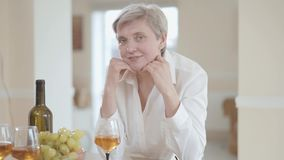 Retrato da mulher superior elegante bonita na blusa branca com o corte de cabelo curto que olha in camera com sorriso agradável d vídeos de arquivo