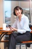Retrato da mulher superior feliz que senta-se no café usando o telefone celular foto de stock