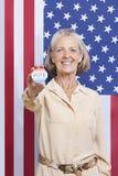 Retrato da mulher superior que mantem o emblema da eleição contra a bandeira americana imagens de stock