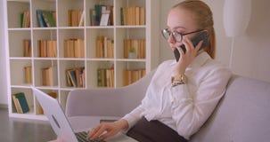Retrato da opinião lateral do close up da mulher de negócios loura caucasiano bonita nova nos vidros usando o portátil e tendo um filme