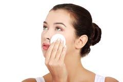 Retrato da pele feliz da limpeza da jovem mulher pela almofada de algodão Fotografia de Stock Royalty Free