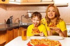 Retrato da pizza pronto para comer do menino e da mãe Fotografia de Stock Royalty Free
