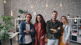 Retrato da posição atrativa da equipe do negócio dos jovens no sorriso do escritório