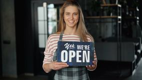 Retrato da posição bonita da menina no café que guarda o sinal aberto que dá boas-vindas a clientes vídeos de arquivo