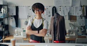 Retrato da posição de sorriso do desenhador de moda feliz da jovem senhora na oficina filme