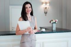 Retrato da posição envelhecida média elegante da mulher na cozinha em casa que guarda papéis em suas mãos imagem de stock