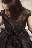 Retrato da princesa moreno nova bonita da mulher no vestido preto que encontra-se para baixo no assoalho Imagem de Stock Royalty Free
