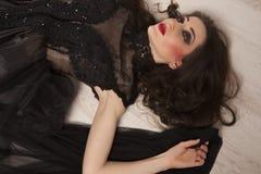 Retrato da princesa moreno nova bonita da mulher no vestido preto que encontra-se para baixo no assoalho Foto de Stock Royalty Free