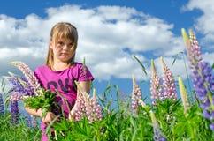Retrato da rapariga no campo de flores do lupine Foto de Stock