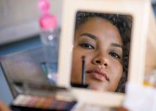 Retrato da reflexão de espelho do estilo de vida da mulher latino-americano feliz e bonita nova que aplica a composição da cara u imagem de stock
