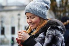 Retrato da rua mulher caucasiano/asiática bonita nova na roupa morna Bebe o chá quente de um copo plástico para manter-se morno imagem de stock royalty free