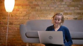 Retrato da senhora caucasiano superior que senta-se no assoalho e que trabalha com o portátil com riso positivo na casa acolhedor fotos de stock