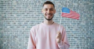 Retrato da terra arrendada americana orgulhosa do indivíduo que voa a bandeira dos E.U. no fundo da parede de tijolo vídeos de arquivo