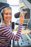 Retrato da transmissão de rádio fêmea feliz do anfitrião Imagem de Stock Royalty Free