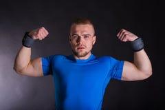 Retrato da vista dianteira de um homem irritado que está mostrando seus músculos sobre o fundo escuro do estúdio Imagens de Stock Royalty Free