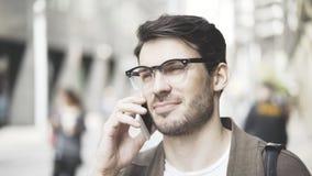 Retrato da vista dianteira de um homem de negócios que fala seu telefone esperto na rua Imagem de Stock