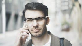 Retrato da vista dianteira de um homem de negócios que fala seu telefone esperto na rua e que olha a câmera Foto de Stock