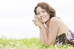 Retrato da vista lateral da jovem mulher que encontra-se na grama contra o céu claro imagem de stock