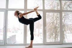 Retrato da vista lateral da mulher loura nova atrativa que dá certo no clube de aptidão ou em casa, fazendo a ioga que está em Na foto de stock