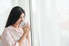 Retrato da vista lateral uma vista de pensamento da mulher bonita guardando uma caneca de café ao lado de uma janela em casa imagem de stock