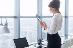 Retrato da vista traseira de um trabalhador de escritório fêmea novo que usa apps em seu tablet pc, terno formal vestindo, estand Fotografia de Stock Royalty Free