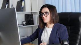 Retrato da vista traseira de uma mulher de negócios que senta-se em seu local de trabalho no escritório filme