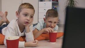 Retrato das crianças bonitas que encontram-se no assoalho em descansos alaranjados na sala que come a pipoca deliciosa e a vista filme