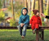 Retrato das crianças no banco no parque, almoço para fora Fotografia de Stock Royalty Free
